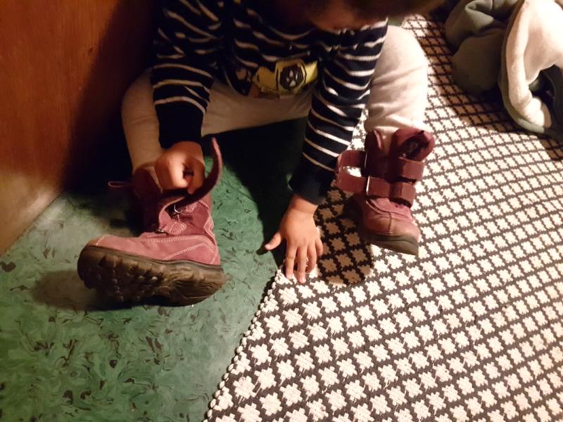 Kind zieht Schuhe selbst an