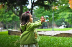 Kind fängt Seifenblase
